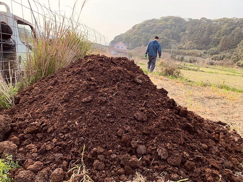 鋤き込まれるのを待つ堆肥